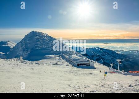 Les montagnes d'hiver. Les sommets enneigés et le brouillard dans les vallées. Grand soleil dans le ciel bleu sur la piste de ski. Ascenseur et bar de ski