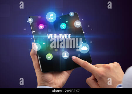 Portrait d'un smartphone pliable avec inscription DANS LE MONDE ENTIER, les médias sociaux concept