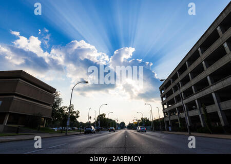 Rayons de soleil qui brille à travers les nuages sur une belle journée d'été dans une ville. Banque D'Images
