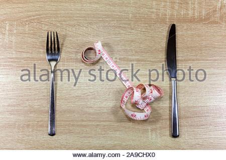 Suivre un régime concept avec couteau, fourchette et ruban à mesurer Banque D'Images