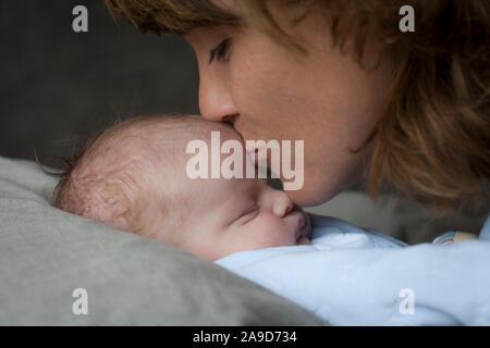 Mère de câlins avec bébé endormi, embrassant le front de bébé, fond sombre Banque D'Images