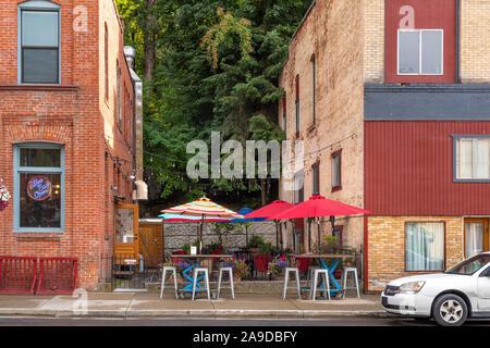 Un petit café terrasse avec parasols colorés est pris en sandwich entre deux bâtiments de brique dans la ville historique de Wallace, de l'Idaho. Banque D'Images