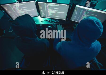 Vue arrière des deux pirates informatiques en hoodies de taper au clavier et de briser le système informatique tout en restant assis dans le bureau sombre Banque D'Images