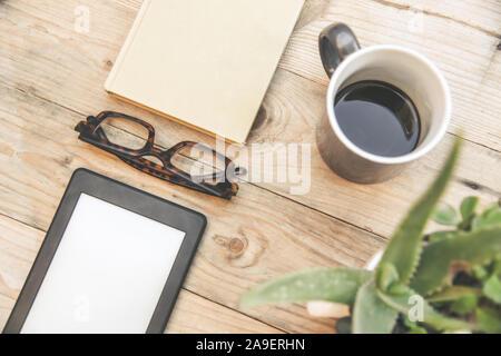 La vie encore Vue de dessus de la nouvelle technologie du livre électronique à côté d'une réserve et les lunettes sur une table en bois et d'un livre vert de l'usine d'aloès. Nouveau périphérique sans fil de haute technologie Banque D'Images