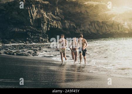 Les adolescents s'exécutant dans l'eau de l'océan au coucher du soleil. Groupe d'adolescents bénéficiant de l'école pause à l'heureux dans la mer. Les gens aiment avoir de vacances fu