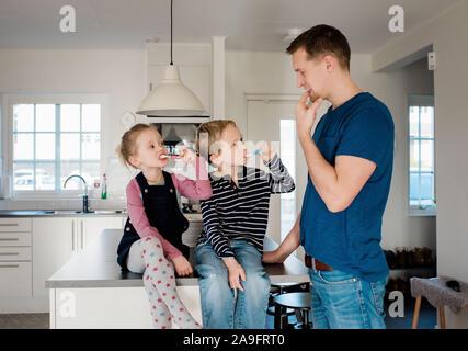 L'enseignement de son père aux enfants comment se brosser les dents avant l'école Banque D'Images