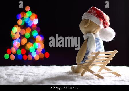 Ours en peluche brun wearing scarf et santa hat assis sur banc en bois avec de la neige en hiver à la recherche de lumières colorées au flou d'arbre de Noël. Banque D'Images