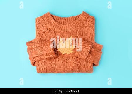 Des feuilles d'automne jaune sur fond orange chandail tricoté à plat, vue de dessus. Banque D'Images