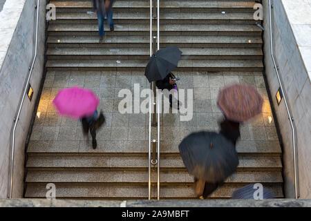 Vue aérienne de personnes à pied de l'éloigner de l'entrée de la gare souterraine sous la pluie avec des parapluies - mauvais temps Banque D'Images