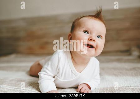 Heureux infant baby crawling on bed smiling adorable Enfant cheveux gingembre de 3 mois de vie de la famille des émotions positives pour enfants Banque D'Images