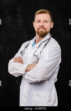 Jeune médecin barbu dans blanchon crossing arms sur la poitrine dans l'isolement Banque D'Images