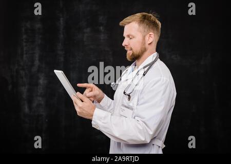 Jeune médecin barbu dans blanchon le défilement en pavé ou pointant sur écran Banque D'Images
