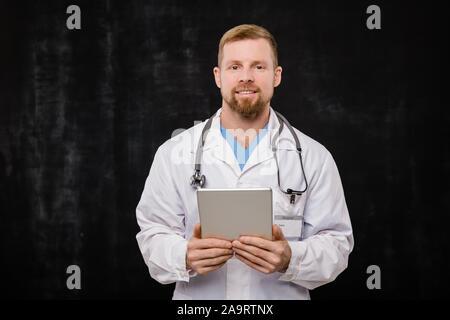 Jeune médecin barbu dans blanchon holding digital tablet par ceinture Banque D'Images