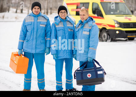 Brigade de jeunes paramédics en vêtements et gants bleu holding trousses de premiers secours Banque D'Images