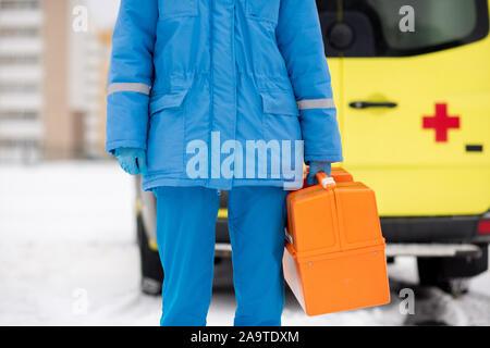 La mi-section de jeunes paramedic en bleu et des gants de travail holding trousse de premiers soins Banque D'Images