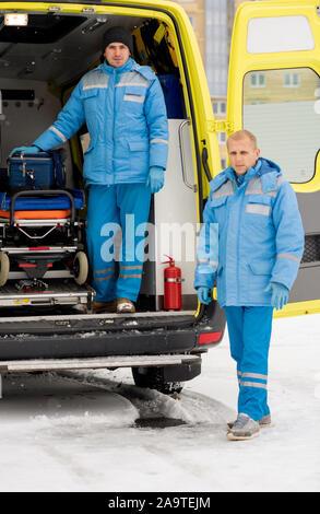 Deux jeunes hommes paramédics en workwear standing in front of camera pendant le travail Banque D'Images