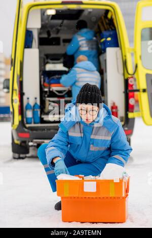 En bleu paramédic et des gants de travail à la médecine dans une trousse de premiers secours Banque D'Images