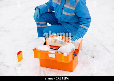 Les jeunes de paramédic et des gants de travail et de la médecine de contrôle de l'aide première Banque D'Images