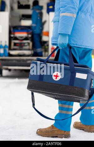 Les jeunes en bleu paramédic et vêtements Gants médicaux exerçant son kit de premiers soins Banque D'Images