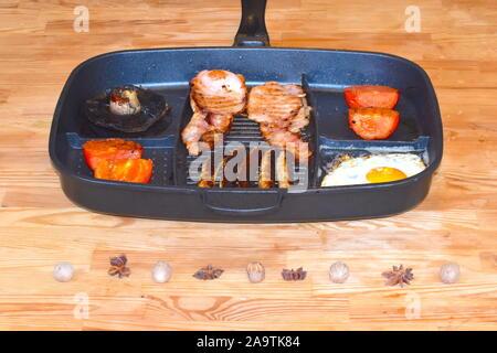 Le petit déjeuner anglais complet pour 2. Oeufs frits, champignons, tomates, saucisses et bacon dans le moule sur une table en bois. Banque D'Images