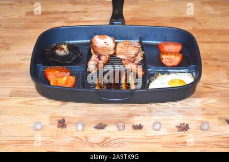 Pan petit-déjeuner pour deux personnes. Petit-déjeuner complet y compris les champignons, saucisses, bacon, oeufs au plat et tomates, sur la table de cuisine en bois. Banque D'Images
