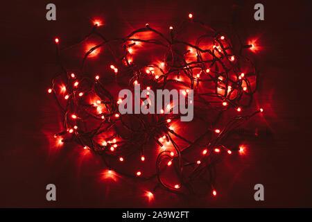 Lumières de Noël rouge sur une table en bois. Rouge vif brillant. Désorganisé led rouge s'allume.