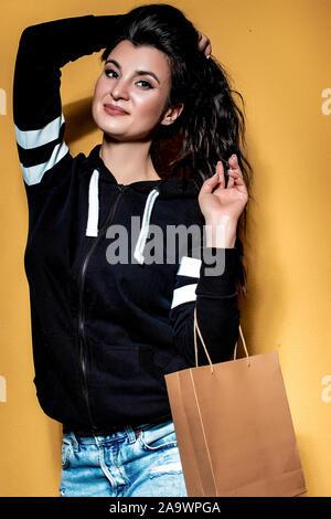 Happy brunette girl est titulaire d'un achat dans un sac d'artisanat sur fond orange.