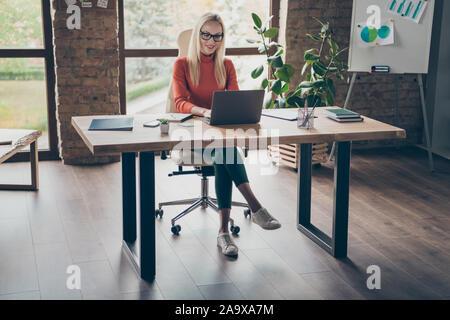 Corps plein de photos charmante femme propriétaire d'entreprise réussie table sit pour l'ordinateur portable de travail Projet de démarrage porter du rouge à col roulé loft bureau de travail