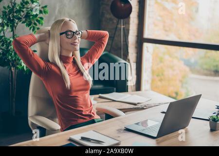 Positive pacifique manager exécutif femme fait tout son travail se détendre reste assis les yeux Fermer table bureau en col roulé rouge loft