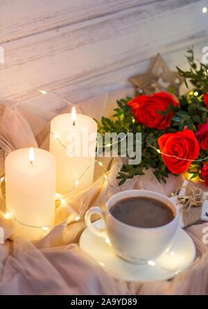 Composition: roses rouges avec buis, guirlandes, bougies, étoiles et tasse café (thé) Banque D'Images