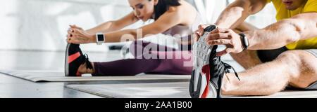 Vue panoramique de tir sportif et de la sportive s'étend sur des tapis de fitness dans sports centre Banque D'Images