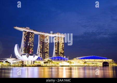 Vue imprenable sur la Marina Bay skyline avec de beaux gratte-ciels illuminés au cours d'un splendide coucher de soleil à Singapour.