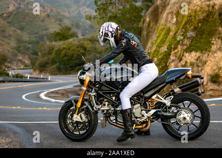 Femme sur la moto se préparer pour descendre winding road Banque D'Images