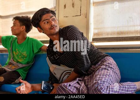 Deux jeunes vendeurs birmans prennent une pause et vérifier un téléphone mobile alors que sur un train local sur la route circulaire autour de Yangon, Myanmar (Birmanie) Banque D'Images