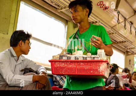 Birman jeune vendeur vend ses marchandises vers le bas-côté d'un train à partir d'un panier en plastique tout en montant le train qui encercle le centre de Yangon, Myanmar (Birmanie) Banque D'Images