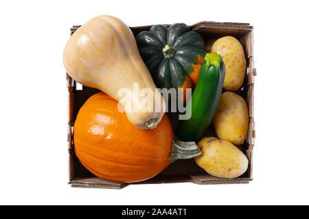 Légumes close up. Produits frais bio, citrouille, courge poivrée, courge Butternut, courgette, et les pommes de terre dans une boîte en bois close up, vue du dessus, isolé Banque D'Images