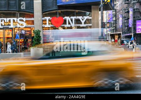 J'aime New York cadeaux signe et taxi jaune floue passant, Times Square, Manhattan, New York, USA Banque D'Images