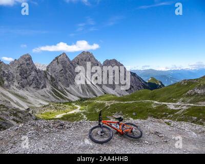 Vtt gisant au bord d'une route de gravier dans les hautes montagnes de Dolomites de Lienz, Autriche. Les pentes sont stériles avec peu d'herbe sur lui. Banque D'Images