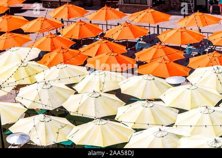 De nombreux parasols high angle orange jaune d'oiseau de l'antenne vue rapprochée au café ou restaurant en ville pendant la journée avec des ampoules suspendues Banque D'Images