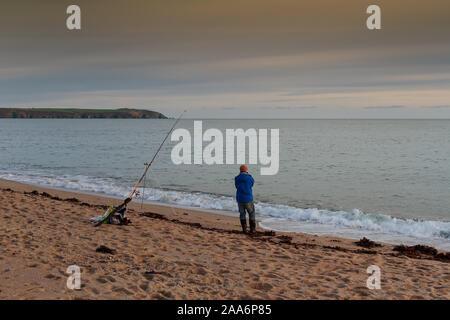 Un pêcheur solitaire est à la recherche à la mer durant le coucher du soleil à St Austell, Cornwall, Royaume-Uni. Banque D'Images