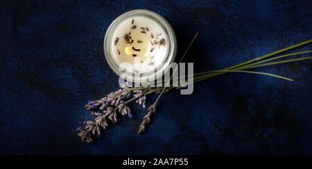 Une bougie parfumée à la lavande, panorama top shot sur un fond sombre avec une place pour le texte. Concept de Noël sans déchets Banque D'Images