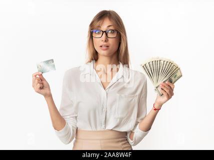 Surpris femme debout de la détention de monnaie et carte de crédit, Studio Shot Banque D'Images