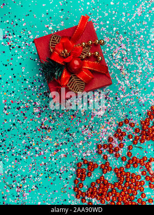 Boîte cadeau rouge avec décoration rouge sur fond bleu turquoise avec des paillettes colorées, les cônes. Maison de concept. Voir Topo Banque D'Images
