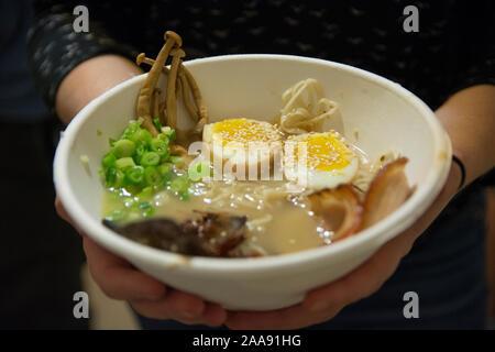 Femme mains tenant un bol de porc soupe ramen japonais traditionnel, avec les champignons Enoki, moyen d'œufs durs, oignon vert, les algues et la viande de porc Banque D'Images