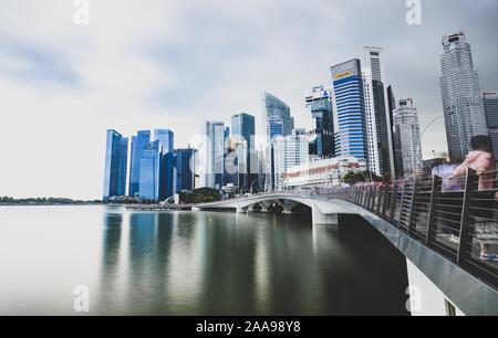 Superbe vue sur le quartier financier de Singapour pendant une journée nuageuse avec la statue du Merlion dans la distance.