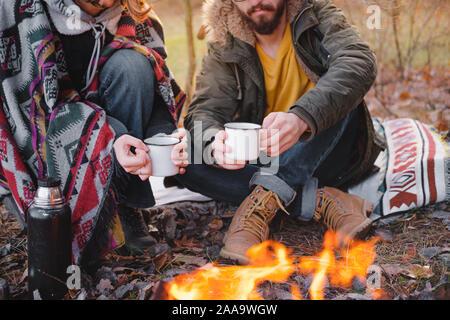 Deux personnes ayant un beau temps à l'extérieur avec un animal à l'automne. L'homme et la femme dans des vêtements chauds s'asseoir en plein air avec leur chien sur une belle chilly d Banque D'Images