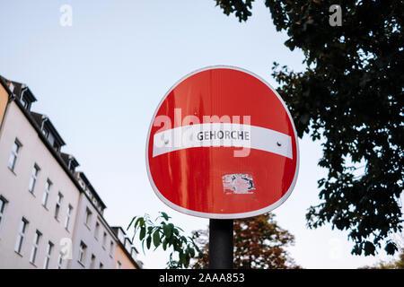 'Quitter' aucun signe d'une rue à sens unique avec un autocollant disant 'Gehorche' ('obéir' en allemand), placé par un artiste de rue Banque D'Images
