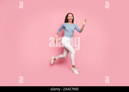 La taille du corps tourné sur toute la longueur de la photo mode positif femme courir vers dream en exprimant l'excitation sur le visage de la chaussure rose isolé