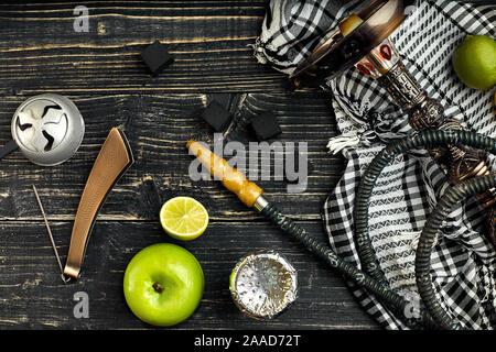 Narguilé arabe avec une saveur de tabac d'un mélange de chaux et d'Apple. Vue de dessus d'un fond en bois foncé Banque D'Images