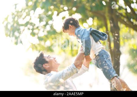 Cute little asian boy levé par le père à l'extérieur dans le parc Banque D'Images